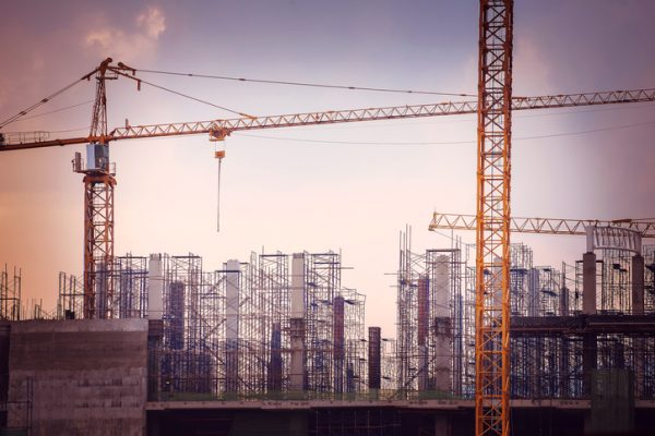 Image of tall cranes with a backdrop of steel framing of buildings